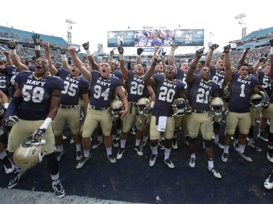 FILE - In this Nov. 5, 2016, file photo, Navy players celebrate after defeating Notre Dame 28-27 in an NCAA college football game Saturday, Nov. 5, 2016, in Jacksonville, Fla. If Navy is in position to earn a spot in a major bowl game when the rankings and semifinal pairings are set Sunday, the 12-person committee will wait a week for Navy to play Army to make a final call on where the Midshipmen should be ranked. (AP Photo/John Raoux, File)