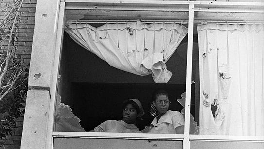 Two Jackson State University students stare out a dormitory