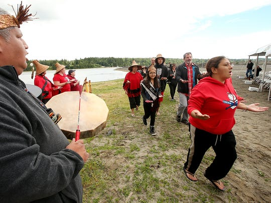 Joe Price, left, plays the drum and sings as fellow Port Gamble S'Klallam Tribe canoe family members and others in attendance dance during Thursday's celebration.