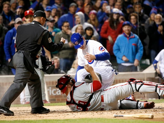 Home plate umpire Toby Basner (99) calls Chicago Cubs' Anthony Rizzo out at home after Philadelphia Phillies catcher Cameron Rupp took a throw from second baseman Cesar Hernandez during the fourth inning of a baseball game, Tuesday, May 2, 2017, in Chicago. (AP Photo/Charles Rex Arbogast)