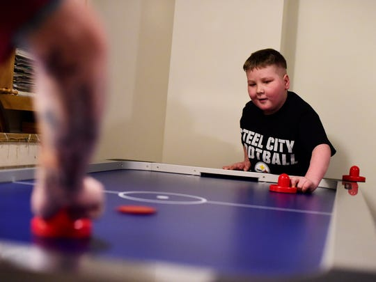 Ayden Zeigler-Kohler plays air hockey at home toward the end of February. Though his balance and motor skills were deteriorated from two cancerous tumors, Ayden was able to keep himself upright by using the wall behind him to balance.