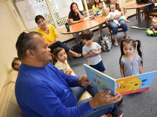 Frank Aflague, a program coordinator for the Guam Public Library System, guides children through a counting story during a toddler program at the Nieves M. Flores Memorial Library in Hagåtña on May 31, 2017.
