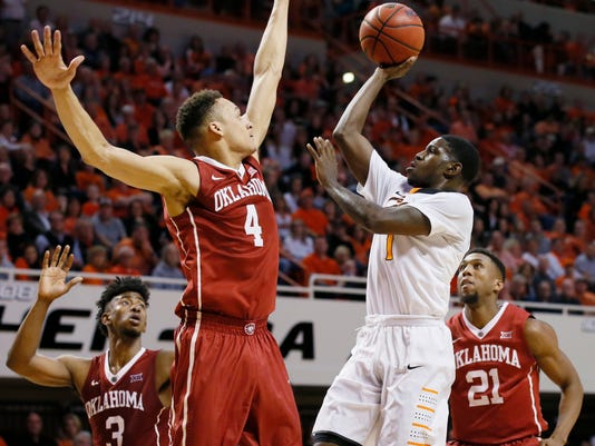 Oklahoma State guard Jawun Evans, right, shoots as Oklahoma center Jamuni McNeace (4) defends in the first half of an NCAA college basketball game in Stillwater, Okla., Saturday, Feb. 18, 2017. (AP Photo/Sue Ogrocki)
