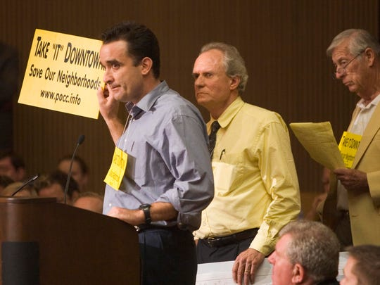 Alex Tauber holds a sign in opposition to Donald Trump's plan during a Phoenix City Council meeting Wednesday night to decide the fate of a proposed 150-foot-tall hotel-condominium project near 24th St. and Camelback Rd.