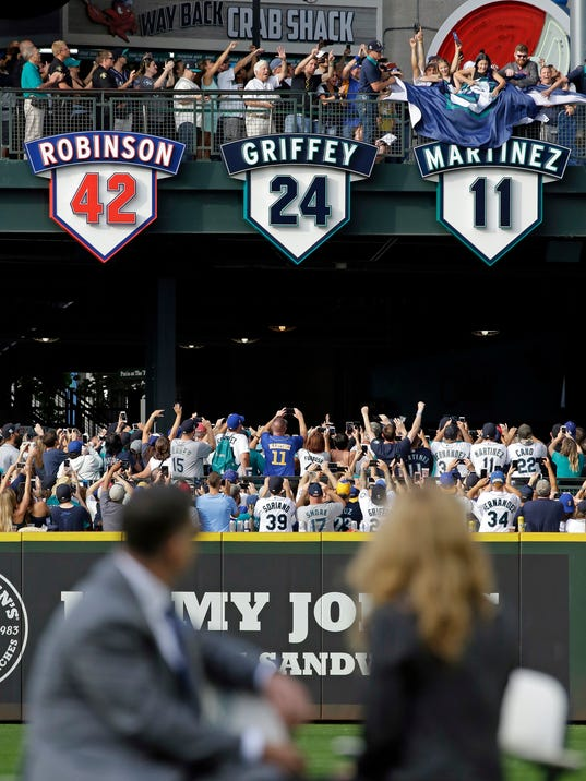 Former designated hitter Edgar Martinez, left, sits with his wife Holli Martinez as they watch the unveiling of his No. 11 during a ceremony retiring the number before a baseball game between the Mariners and Los Angeles Angels, Saturday, Aug. 12, 2017, in Seattle. (AP Photo/Elaine Thompson)