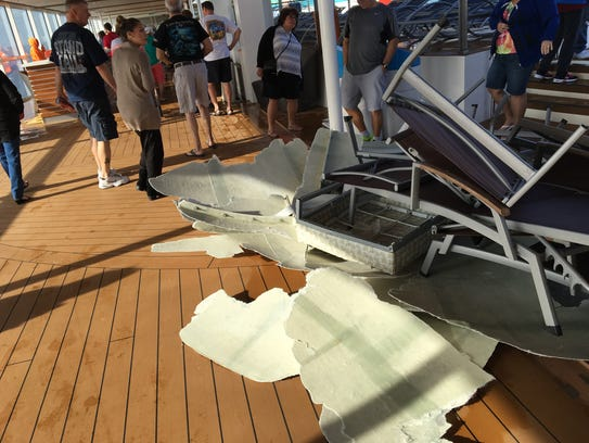 Passengers walk around storm-tossed furniture on the