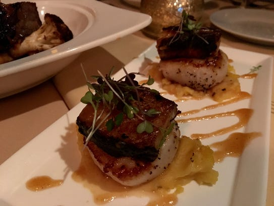Squares of pork belly sit atop plump scallops and a