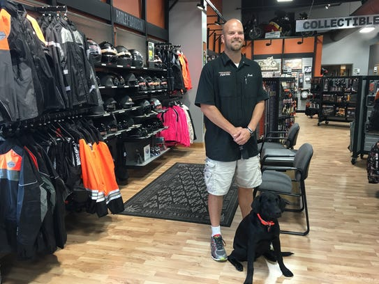 An employee's friendly dog poses along with Harley-Davidson