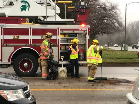 Firefighters clean up after a driver of a pickup hit