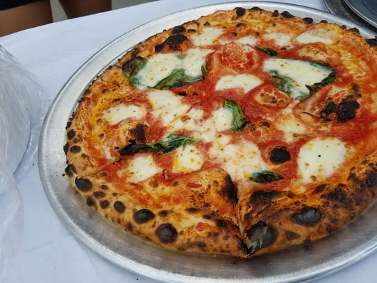 Wood-fired pizza sporting fresh basil and freshly pulled