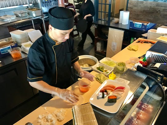 One of Ichiyummy's sushi chefs preps a plate of sushi