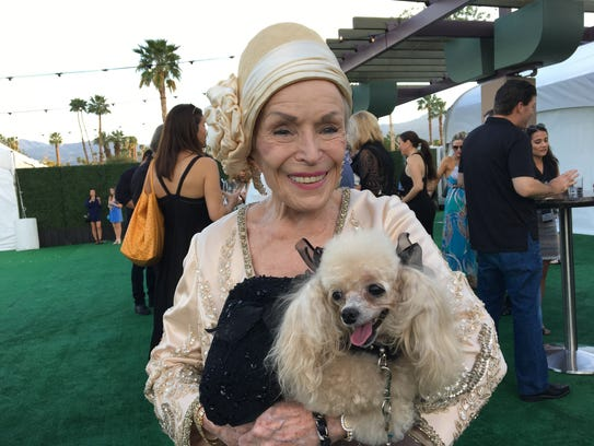 An attendee with her dog before a canine couture show