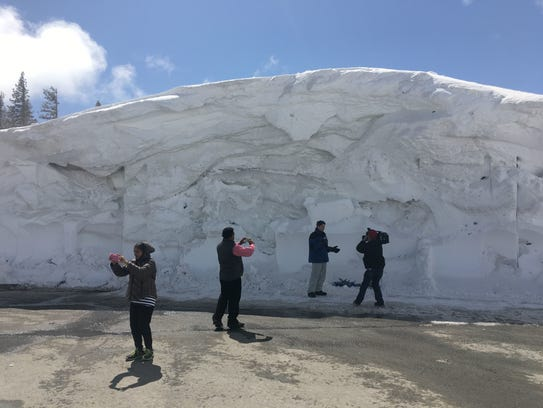 People photograph a massive snowbank at the Mt. Rose