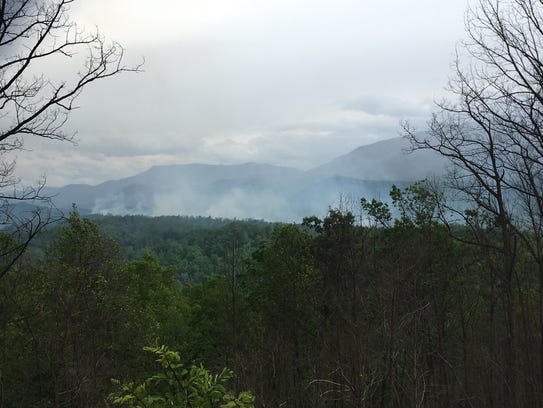 Smoke rises through the mountain tops from a wildfire