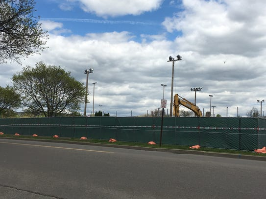 Fencing surrounds the tennis court area of Elmira High