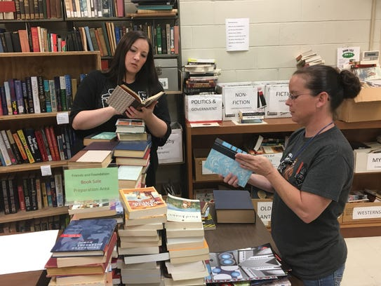 Jenci Spradlin, left, and Zoe Pride sort books for