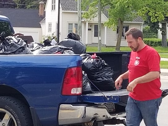 Kyle Bryntesen loads garbage into a truck for one of