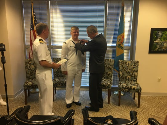"""Sen. Tom Carper pins the """"dolphin"""" medal, which signifies"""