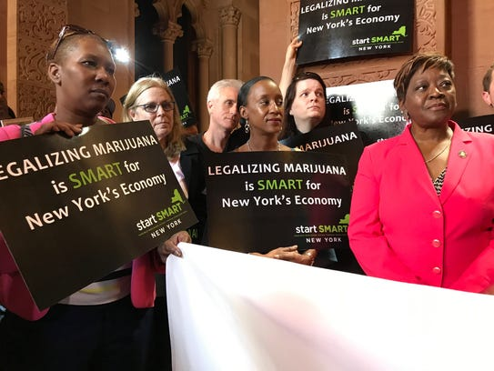Assemblywoman Crystal Peoples-Stokes, right, stands
