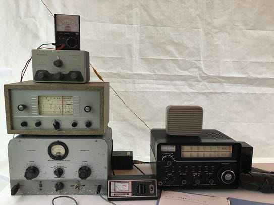 A stack of old radios, transmitters and other equipment.