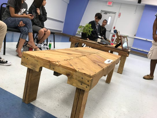 Students show coffee tables constructed from reclaimed