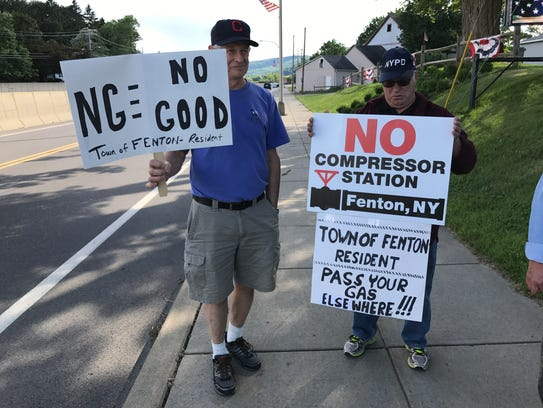 Don McDufee, left, and Kurt Mohney protest the construction