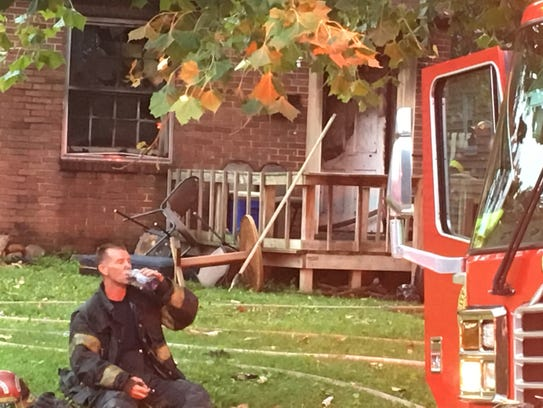 A Knoxville firefighter takes a break after extinguishing