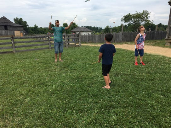 A group of children and a parent play with old fashioned