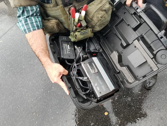 A bomb squad officer holds the suspicious package,