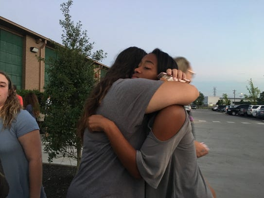 Attendees embrace at a vigil at Experience Community