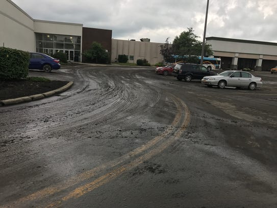 Mud and other sediments cover the road in the parking