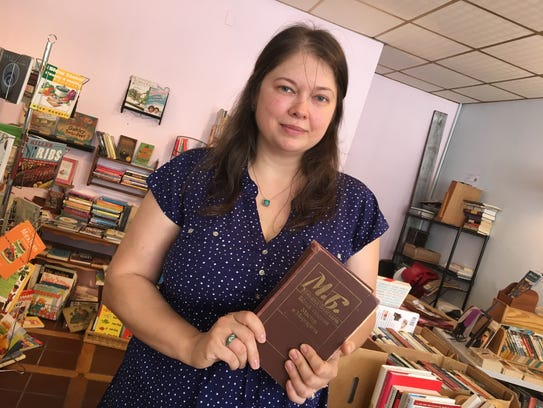 Julia Sabin, co-owner of Staunton books, holds up a