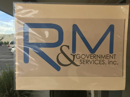 R & M Government Services logo hangs inside the door