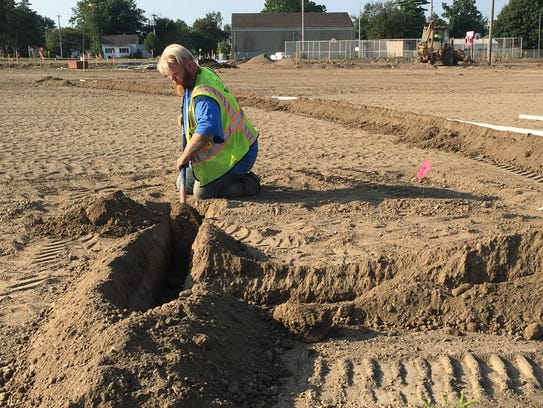 A construction worker digs a trench for new recreational