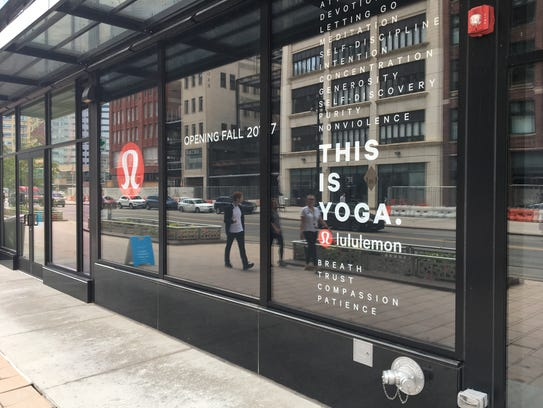 New window signs announce the coming arrival of a Lululemon