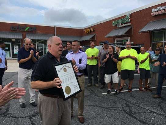 Gov. Larry Hogan holds a governor's citation that was