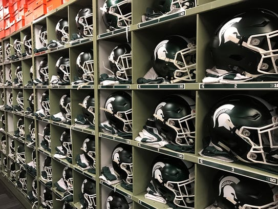 Rows of MSU helmets and jerseys sit inside cubbies
