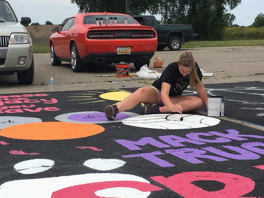 Mackenzie Desloover, 17, paints finishing touches on