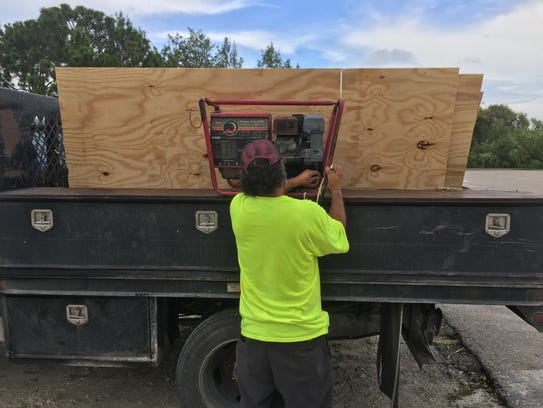 Jaime Espinoza of Immokalee loads plywood into the