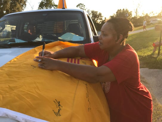 A Florida resident signs the New Mexico flag that Joseph