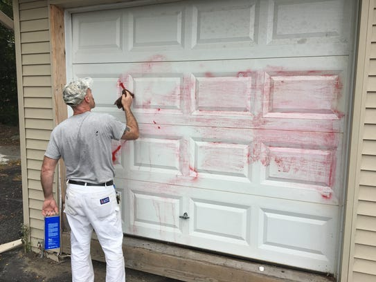 A man uses paint thinner to remove red graffiti Sept.