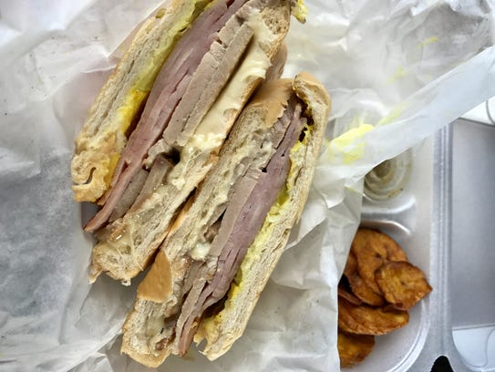 A sandwich Cubano with plantains and mojo sauce from