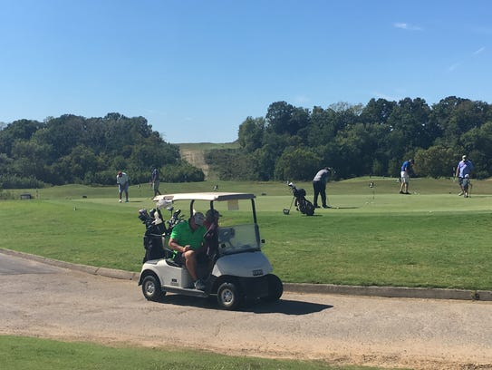 Golfers drive to their next hole at The Crossing Golf
