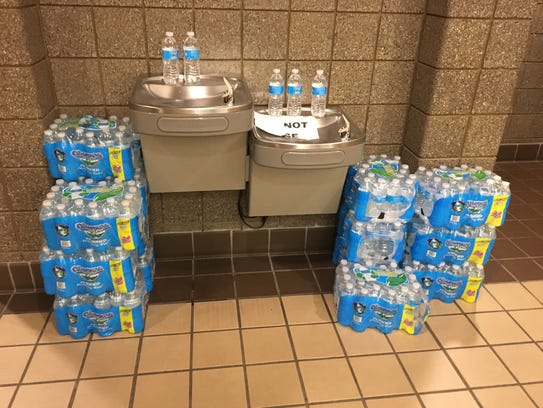 Cases of water surround the the drinking fountain at