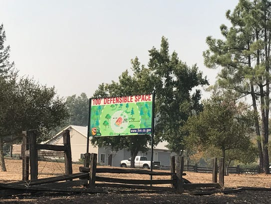 A defensible space sign above a burned fence in Sonoma
