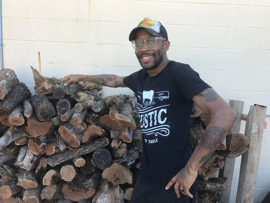 Courtney Hampton, owner and culinary guru behind Rustic, stands by his wood pile.