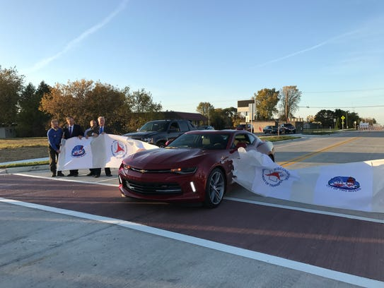 A red Corvette drives through a banner to commemorate