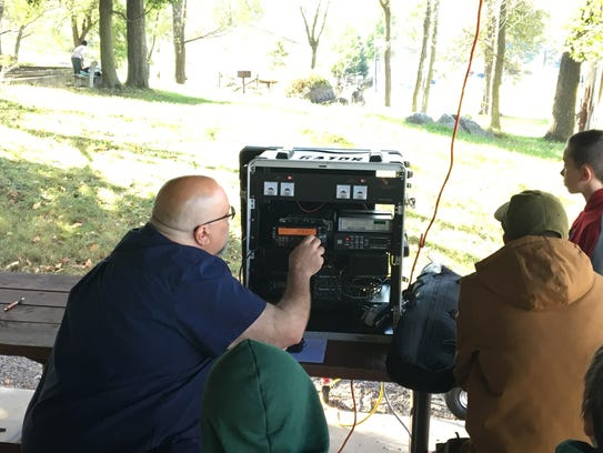 A ham radio operator shows area boy scouts how to operate