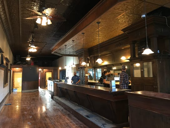 Workers clean Brew Mill's back bar in Menasha.