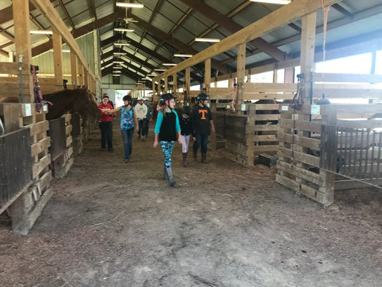 Girl scouts walk through the equestrian facility at Camp Sycamore Hills in Ashland City, which typically holds about 40 horses.